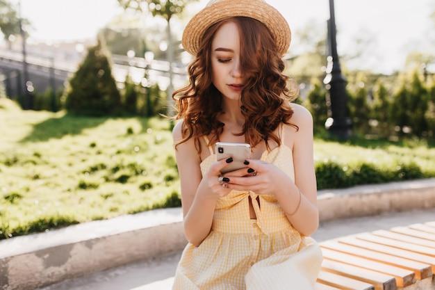 Espetacular jovem na mensagem de mensagens de texto de chapéu na moda enquanto está sentado no belo parque. foto ao ar livre de garota elegante com cabelo ruivo, esperando alguém no banco.