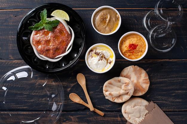 Espetada crua com acompanhamentos, homus, babaganoush, requeijão e pão pita. comida árabe. embalagem de entrega