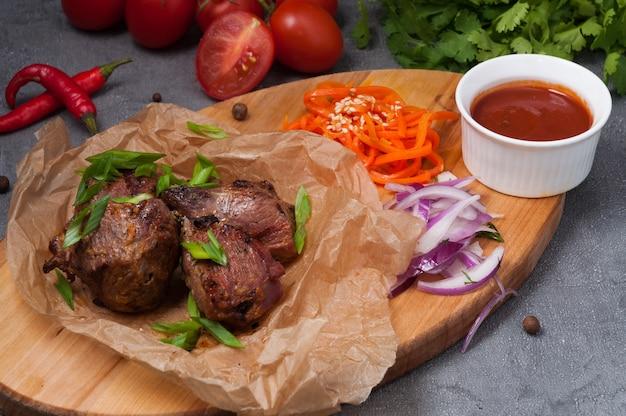 Espetada de carne com cebola roxa, cenoura e molho de tomate