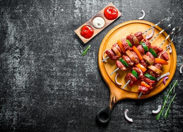 Espetada de carne crua com vegetais em uma tábua de corte com molhos, alecrim e fatias de cebola