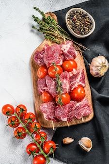 Espetada de carne crua na tábua. churrasco com tomate e especiarias. plano de fundo cinza. vista do topo.