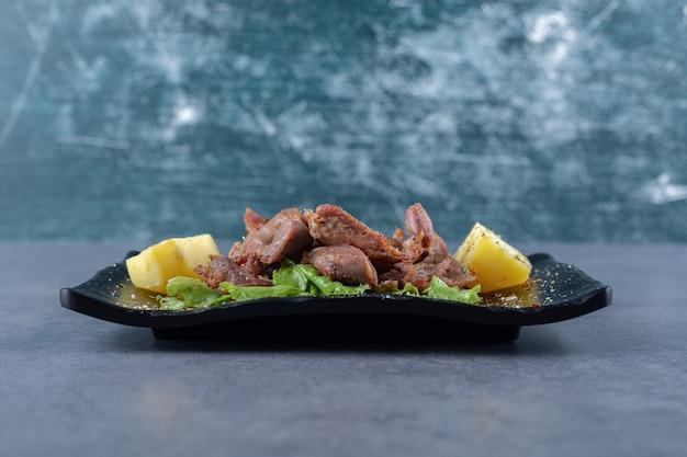 Espetada de carne e batatas cozidas na placa preta.
