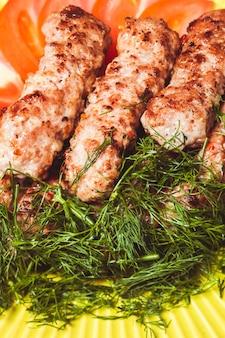 Espetada de carne picada com endro verde e tomate em um prato