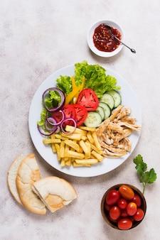 Espetada de carnes e vegetais cozidos em vários pratos