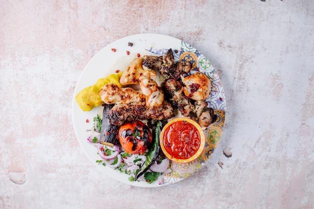 Espetada de frango com legumes grelhados e molho barbecue.