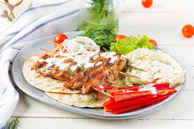 Espetada de frango grelhado com pão sírio e legumes frescos em uma mesa branca