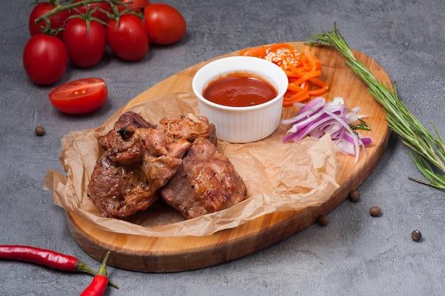 Espetada de pescoço de porco com molho de tomate em uma placa de madeira
