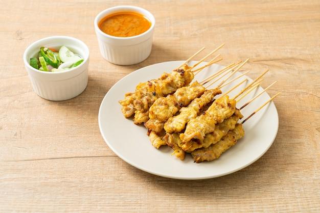 Espetada de porco com picles ao molho de amendoim que são rodelas de pepino e cebolas em vinagre - comida asiática