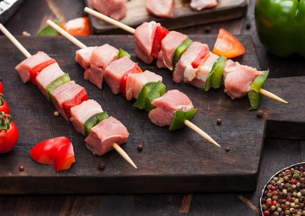 Espetada de porco crua e frango com páprica na tábua de cortar com sal e pimenta na madeira.