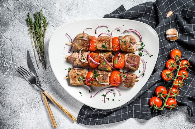Espetada de porco no espeto com tomate e pimenta. comida para um piquenique. plano de fundo cinza. vista do topo.