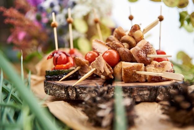 Espetada em varas de madeira, mistura de carne de porco saborosa e legumes, carne grelhada