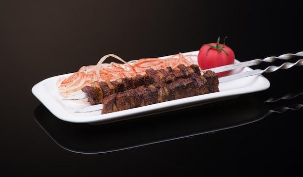 Espetada espetada em espetos com cebola e tomate em fundo escuro