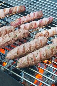 Espetadas com ervas e linguiça de bacon grelhado