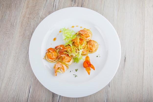 Espetadas de camarão frito em prato branco