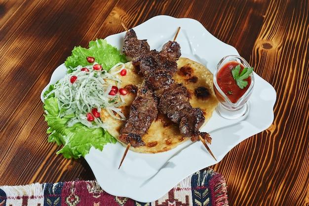 Espetadas de carne de porco em cubos magras grelhadas saudáveis servidas com uma tortilha de milho e salada fresca de alface e tomate, close-up vista