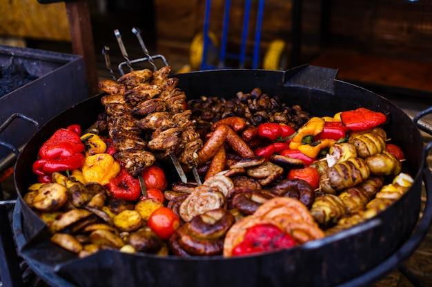Espetadas de legumes coloridas e uma espiga de milho grelhando em um churrasco ao ar livre