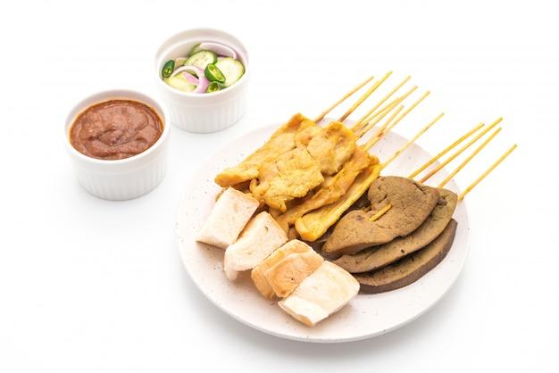 Espetadas de porco com molho de amendoim e picles que são fatias de pepino e cebola em vinagre
