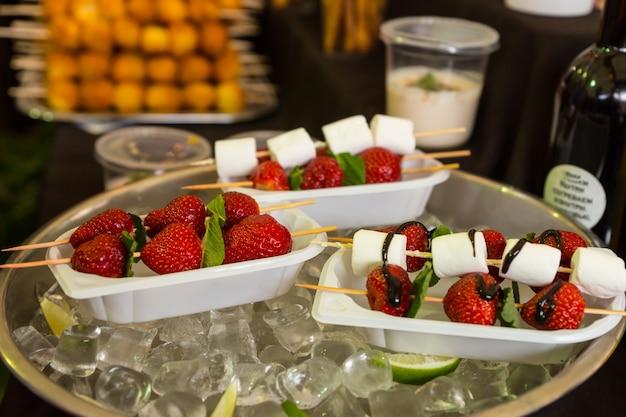 Espetadas de sobremesa individuais de morangos e marshmallows regadas com molho de chocolate servidas em bandejas de comida e mantendo a calma em uma tigela de gelo na mesa do buffet