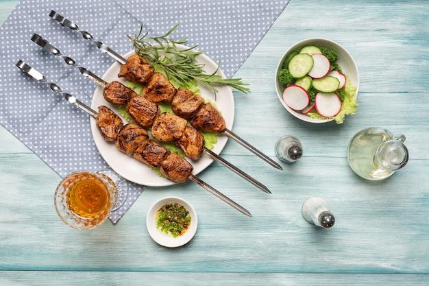 Espetinho caseiro apetitoso, legumes fatiados, uma taça de vinho, vista superior sobre um fundo azul de madeira.