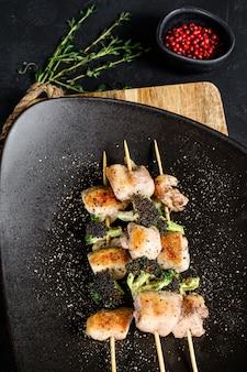 Espetinho caseiro de carne de coxa de frango. fundo preto. vista do topo