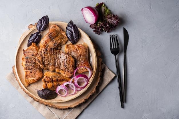Espetinho de bagre shashlik com peixe assado em um prato redondo com cebola roxa e manjericão