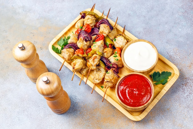 Espetinho de frango com legumes, ketchup, maionese, vista superior
