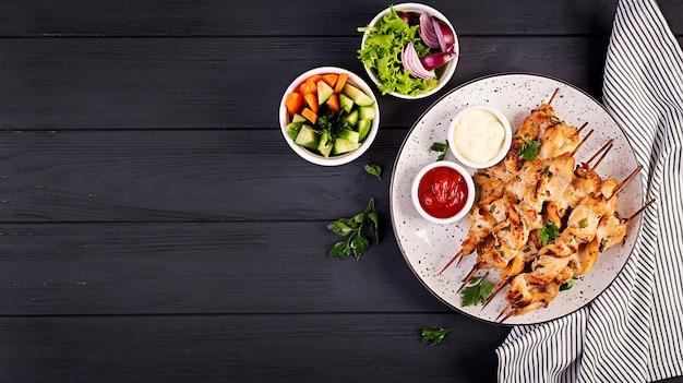 Espetinho de frango. shashlik - carne grelhada e legumes frescos. vista do topo