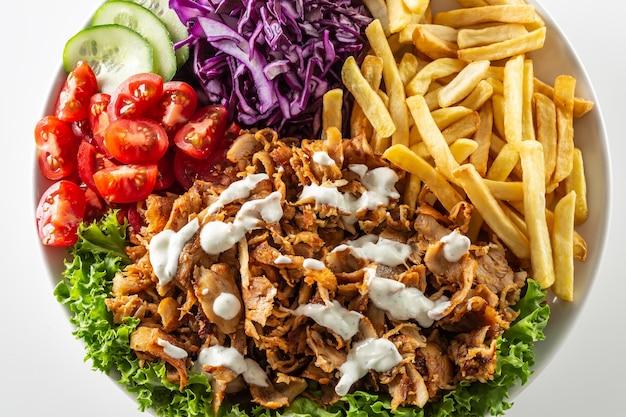 Espetinho de frango turco tradicional isolado preparado com lindas batatas fritas, legumes frescos e molho gostoso.