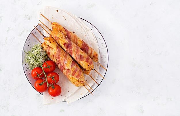 Espetinho de lula picado de peru grelhado (frango) com abóbora embrulhada em bacon no prato. vista superior, sobrecarga