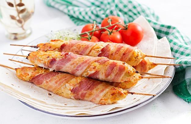 Espetinho de lula picado de peru grelhado (frango) com abóbora embrulhada em bacon no prato.