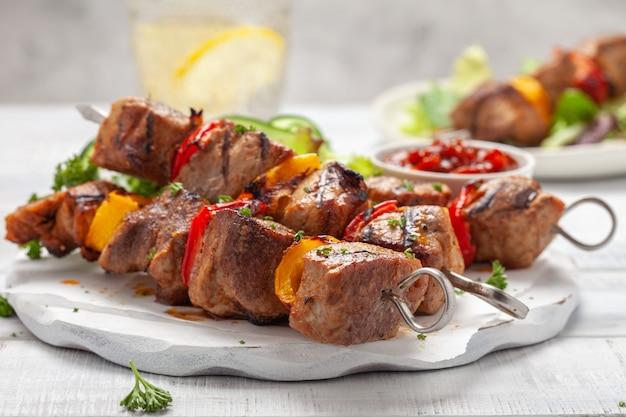 Espetinho de porco grelhado com pimentão vermelho e amarelo