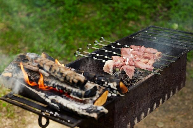 Espetinho de porco no espeto é frito na grelha com lenha quente