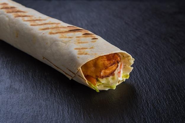 Espetinho de shawarma com bacon na pedra preta texturizada