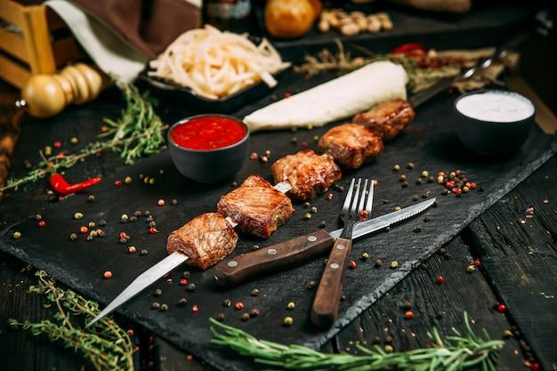 Espetinhos de carne de carneiro apetitosos com molho vermelho e cebola em conserva em um quadro negro