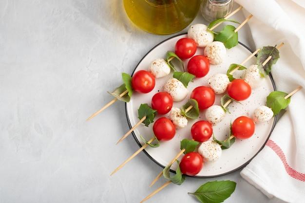 Espeto com tomate, mussarela e manjericão.