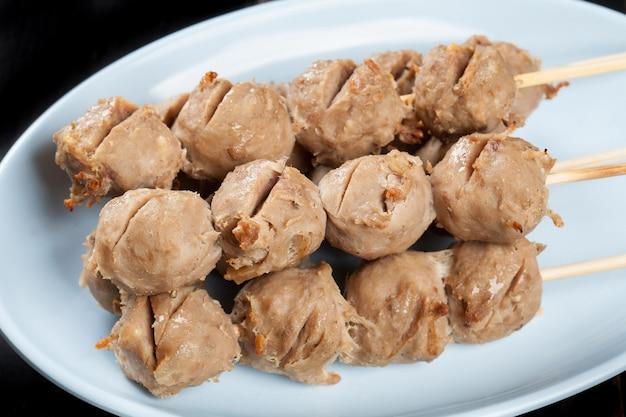 Espeto de almôndegas grelhadas de bambu na placa branca na mesa de madeira, tendão de bolas de carne grelhada comida de rua da tailândia.