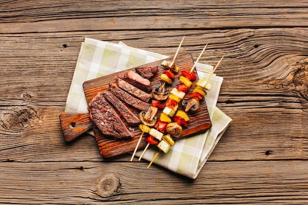 Espeto de carne e fatia de bife frito na tábua de madeira