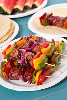 Espeto de churrasco com carne e vegetais na tabela de piquenique