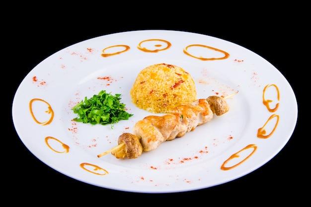 Espeto de frango: filé de frango, pimentão, cogumelos, cuscuz picante com legumes e tomate seco com salsa.
