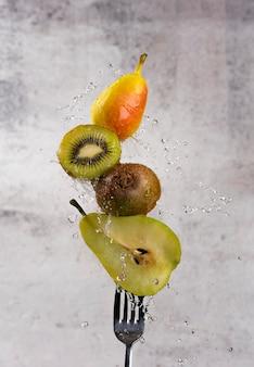 Espeto de frutas em um garfo com gotas de água e respingos. frutas recém cortadas