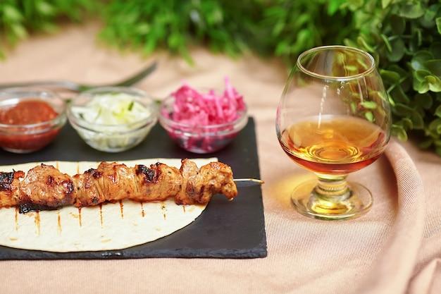 Espeto de quibe shashlik no prato de ardósia, molho, cebola e conhaque