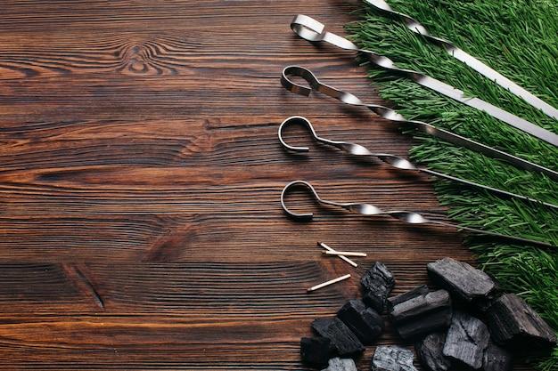 Espeto metálico e carvão no tapete de grama verde sobre a superfície de madeira