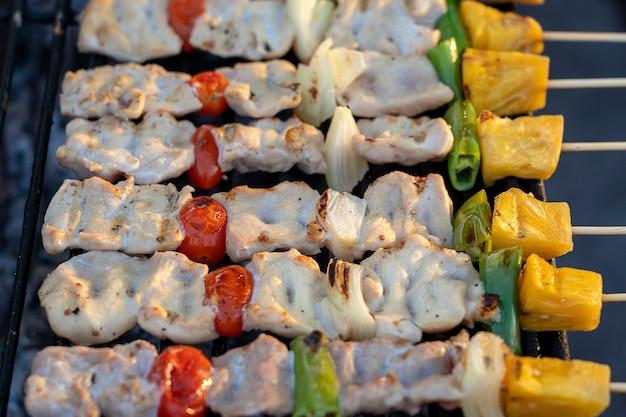 Espetos com pedaços de churrasco na brasa, pimentão verde, tomate vermelho e carne para venda em feirinha, tailândia, close up
