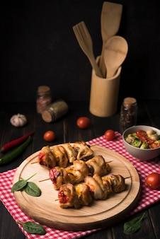 Espetos de alto ângulo na placa de madeira com tomates
