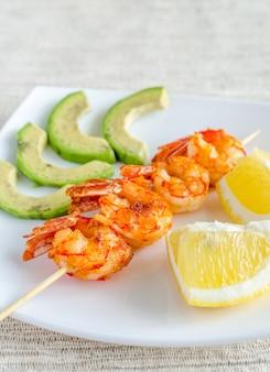 Espetos de camarão com fatias de abacate e limão