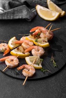Espetos de camarão com frutos do mar e rodelas de limão borradas