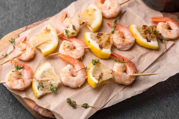 Espetos de camarão e frutos do mar em papel manteiga