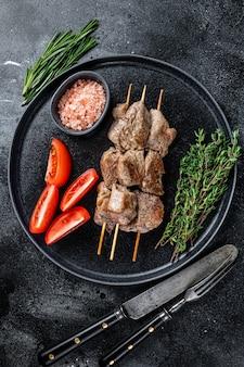Espetos de carne assada no espeto e legumes em um prato. fundo preto. vista do topo.