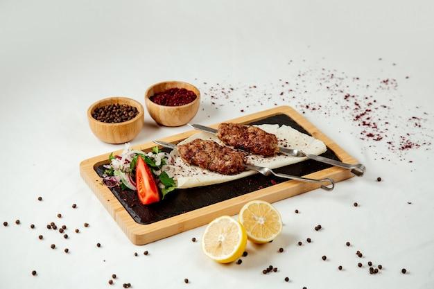 Espetos de carne com cebola em uma placa de madeira