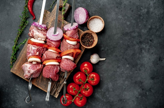 Espetos de carne crua. carne de churrasco com legumes e especiarias.